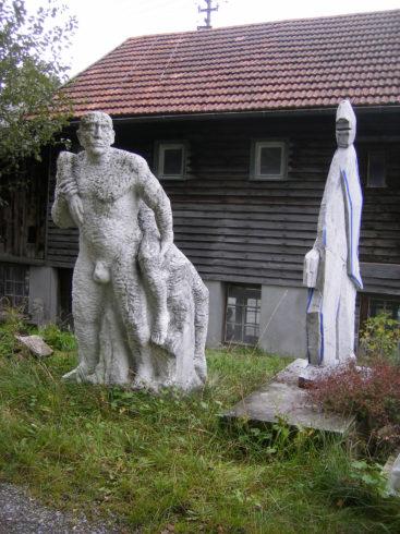 Zwei Arbeiten hinter dem Atelier: Amor & Psyche, Carraramarmor, 205 x 60 x 90 cm, 1989 (links), Schreitende Schmalfigur, Carraramarmor, 200 x 70 x 25 cm, 1994 (rechts); Foto: Anita Brockmann