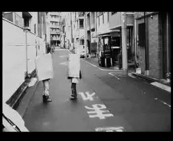 """9. Tokyo Kids, 2012. 1:06 Min. Schwarz-Weiß, Sound. In den Straßen von Tokyo spielen zwei Kinder. Das eine trägt eine Maske mit einem Minus-Zeichen, das andere trägt eine Maske mit einem Plus-Zeichen. Das kindliche Spiel schwankt zwischen Zärtlichkeit und Brutalität. Es bleibt offen, ob die Kinder für die Kamera """"performen"""" oder ob es eine Kamerabeobachtung ist."""