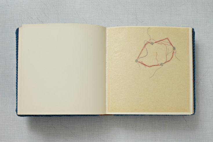 """""""Familienalbum"""", 2011, Fotoalbum mit blauem Garn umhäkelt, mit 38 Nadelstickereien in Pergamentpapier, Buch: 26 x 27 x 4 cm, Tisch: 74 x 90 x 60 cm, © Sylvie Hauptvogel, Foto: Sigurd Steinprinz"""