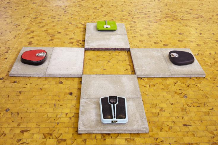"""""""Wie schwer wiegt deine Seele?"""", 2011, Installation mit 4 Körperwaagen, Stickband, 8 Betonplatten, ca. 15 x 150 x 150 cm, © Sylvie Hauptvogel, Foto: Sigurd Steinprinz"""