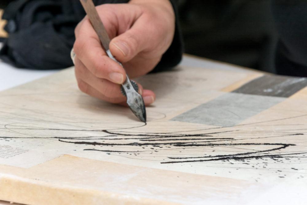 """""""Dem Wunder leise wie einem Vogel die Hand hinhalten."""" Mit Ziehfeder und Airbrushfarbe setzt Birgit Nass das für sie zentrale Wort """"Wunder"""" aus einem Vers von Hilde Domin um. Ganz bewusst spielt sie dabei mit dem Effekt, dass die Airbrushfarbe auf dem Japanpapier verläuft, mit dem die Leinwand beklebt wurde."""